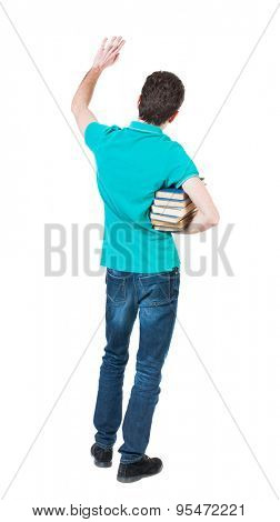 A man carries a heavy pile of books and waves . back view. Rear view people collection. Man holding a heavy stack of books under his right arm in greeting and waving his left hand.