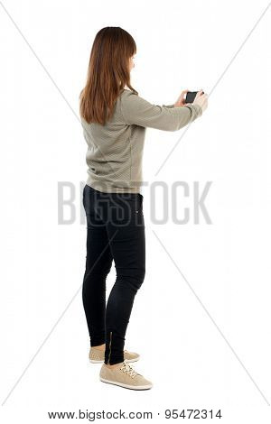 Back view of woman photographing.   girl photographer in jeans. Rear view people collection.   Isolated over white background. A girl in a gray jacket photographs holding the camera at arm's length.