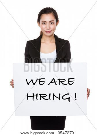 Asian businesswoman showing a board showing with we are hiring phrases