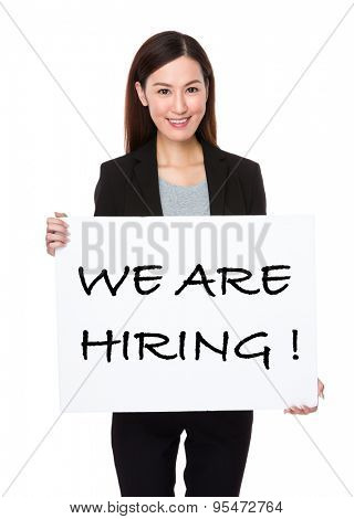 Beautiful businesswoman holding a board showing with looking for a job phrases
