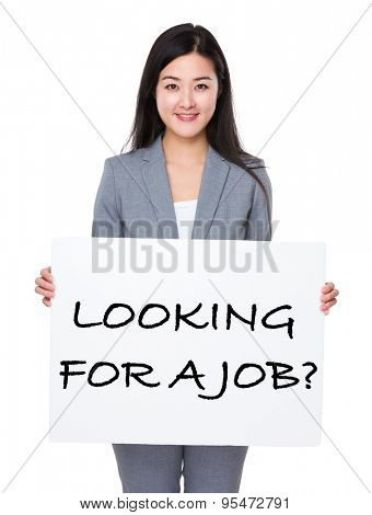 Beautiful businesswoman holding a poster showing with looking for a job phrases