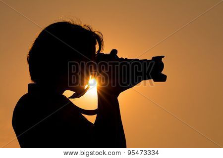 Young woman shooting with a camera against sunset sky, with a sunburst