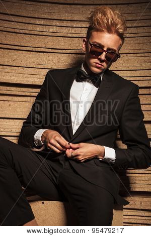 Blond young business man closing his jacket while looking down.