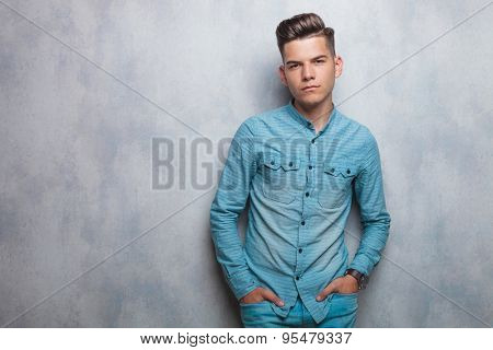 Young casual man holding his hands in pockets while leaning on a grey wall/
