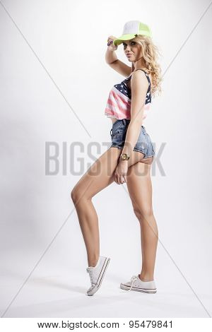 Portrait of a pretty blonde young adult beauty woman posing in American flag shirt and baseball cap isolated on white background