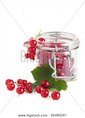 jam glass filled with redcurrant, leaf and more fruit in front, isolated on white background