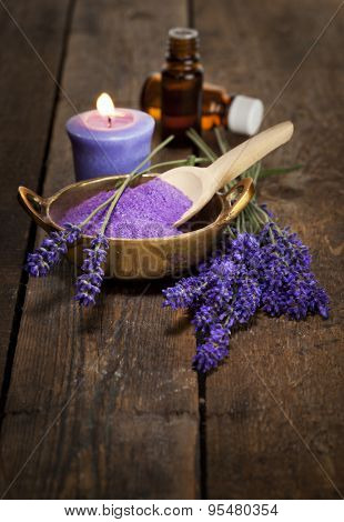 Lavender flowers, bath salt and essential oils on wooden surface