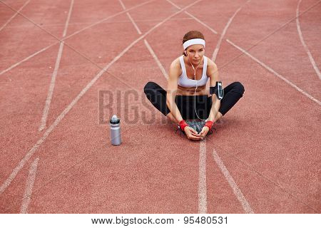 Fit woman in activewear sitting on racetrack