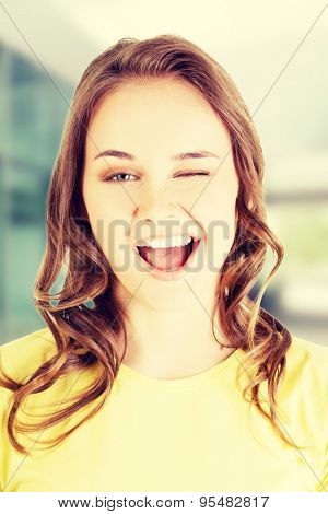 Portrait of young beautiful woman blinks eye