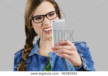 Beautiful woman taking a selfie and making a ugly face, isolated over a grey background