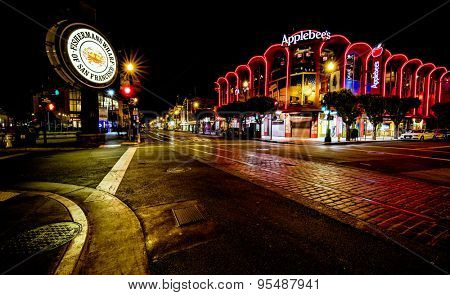 San Francisco, CA, USA - June 25th, 2015: Famous Fisherman's Wharf street and signage at night and Applebee's restaurant.