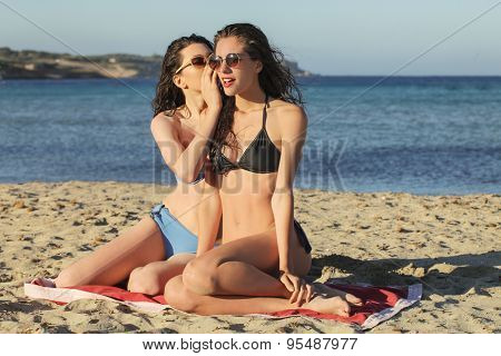 Two girls whispering secrets at the beach