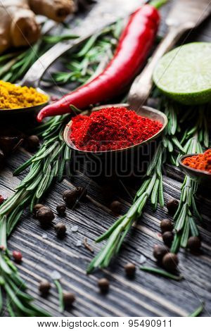 Spices. Herbs and spices selection in old metal spoons over wooden background. Curry, Saffron, pepper and other.