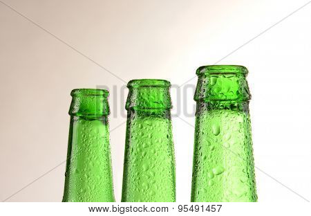 Three green beer bottles covered with condensation. Horizontal format with a warm light to dark background.