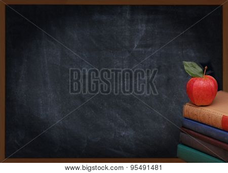 A stack of books with a red apple on top in front of an out of focus chalkboard. Back to school or education concept. Vintage effect with vignette added.