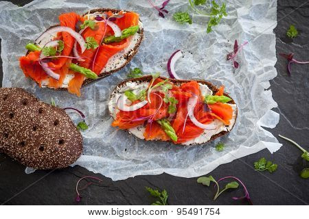 Sandwiches with smoked salmon and asparagus on the black stone background, top view