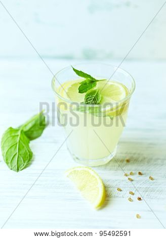 Glass of homemade lemonade with mint and lemon wedges