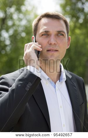 Close up, young businessman calling by phone in summer street