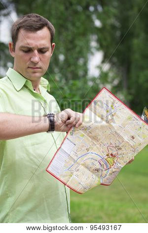 Young male tourist with map in hand looking at wristwatch. Tourist map of the city of Moscow, Russia (no trademark)