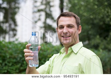 Handsome man drinking water in summer park