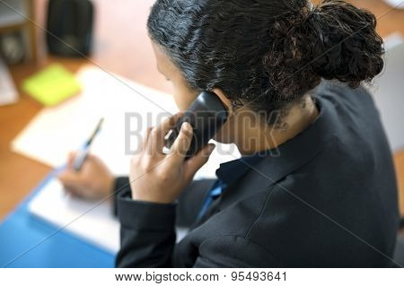 High angle view of receptionist using cordless phone while writing at counter in office