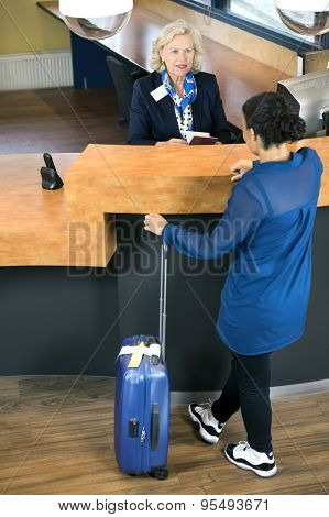 High angle view of woman with luggage standing at hotel reception desk