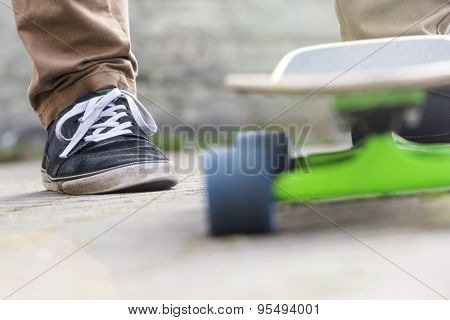 Cropped image of man with skateboard on footpath