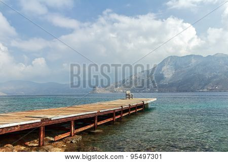 Sea beach coastline with wooden pier on Greek Dodecanese Telendos island