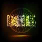 stock photo of indian independence day  - Beautiful glowing text India in tricolors on Ashoka Wheel decorated shiny brown background for Indian Independence Day celebration - JPG