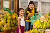 pic of tamarind  - Indian mother and daughter buying sweet tamarind fruit at the grocery store - JPG
