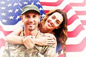 picture of reunited  - Soldier reunited with partner against rippled us flag - JPG