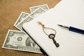 image of memento  - Opened notebook with a blank sheet pen key and money on the old tissue - JPG