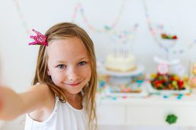 pic of princess crown  - Adorable little girl with princess crown at kids birthday party taking selfie - JPG