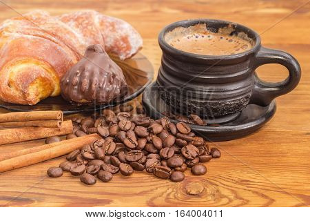 Freshly brewed coffee latte in a black ceramic cup closeup on the background of roasted coffee beans cinnamon sticks chocolate truffle and croissant on an old wooden surface