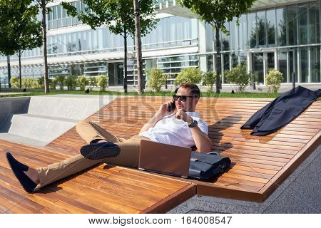 Businessman working on laptop lying on the bench talking on a cell phone