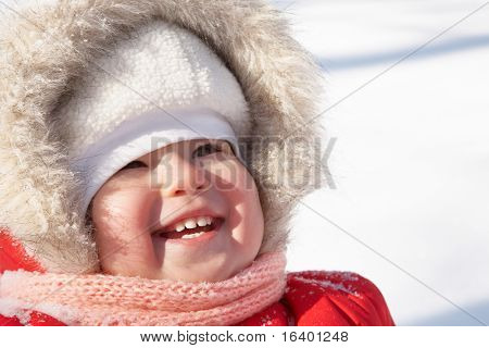 Laughing toddler girl having fun in snow