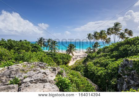 Bottom Bay Barbados - December 18 2016: People on the Bottom Bay beach Barbados Caribbean. It is a tropical paradise with palms hanging over turquoise sea and a pirate cave.