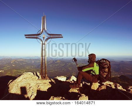 Tired Hiker Sit Bellow Crucifix On Mountain Peak. Iron Cross At Alps Mountain Top.