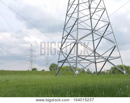 Country landscape with high-voltage power line grey metal pilons with many wires over cloudy sky