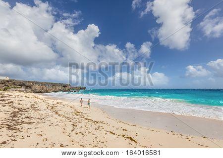 Bottom Bay Barbados - December 18 2016: Couple relaxing on the Bottom Bay beach Barbados Caribbean. Vacation background.