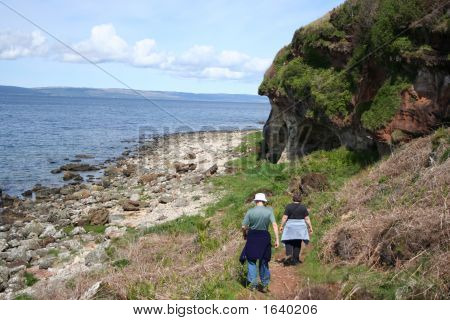 Couple Walking Along Coast