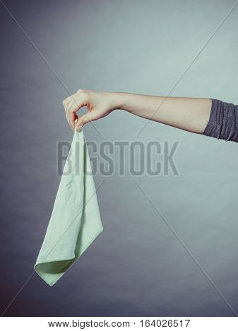 Smell disgusting filth hygiene odor concept. Person holding smelly rag. Female arm keeping filthy tissue away from nose.