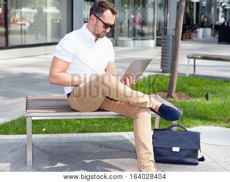 Businessman working on laptop sitting on bench