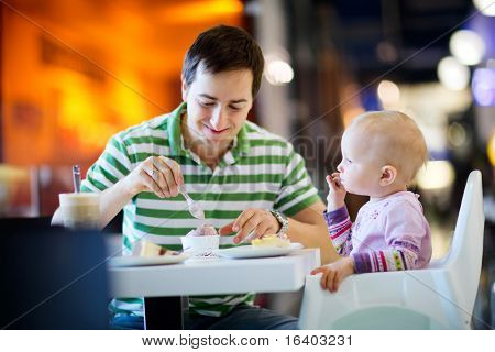 Young father with baby daughter enjoying meal sitting at cafe