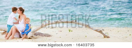 Panoramic photo of young beautiful woman with two kids sitting on tropical beach