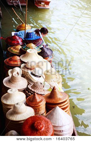 Hat selling on traditional Damnoen Saduak Floating Market near Bangkok in Thailand