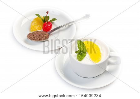 A cup of coffee with grated chocolate orange slices and maraschino cherry