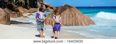 Panoramic photo of family with two kids walking along tropical beach