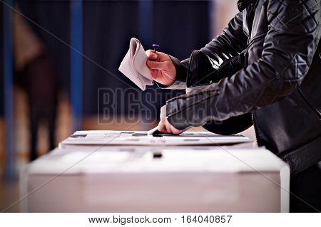 Hands holding a stamp casting a vote into the ballot box during elections