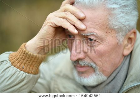 close-up portrait of a senior man thinking about something standing outdoors